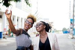 Jeunes femmes prenant des photos de selfie par leur téléphone intelligent Photo stock
