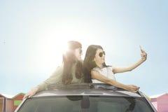 Jeunes femmes prenant la photo de selfie sur le toit ouvrant de voiture Photographie stock libre de droits