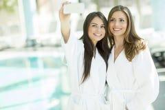 Jeunes femmes prenant le selfie avec le téléphone portable au centre de station thermale Image libre de droits