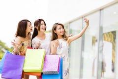jeunes femmes prenant Selfie tout en faisant des emplettes Image libre de droits