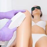 Jeune femme recevant le traitement de laser d'epilation Photographie stock libre de droits