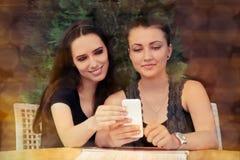 Jeunes femmes regardant l'écran intelligent de téléphone Image libre de droits