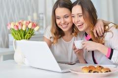 Jeunes femmes regardant l'ordinateur portable Photos libres de droits
