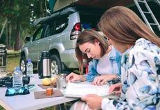 Jeunes femmes regardant la carte de route avec 4x4 dessus Photos stock
