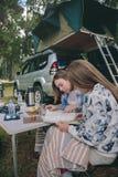 Jeunes femmes regardant la carte de route avec le véhicule sur le fond Image stock