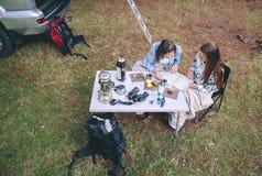 Jeunes femmes regardant la carte de route dans le terrain de camping Photos stock