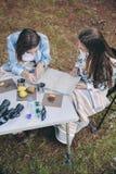 Jeunes femmes regardant la carte de route dans le terrain de camping Photographie stock libre de droits