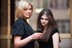 Jeunes femmes regardant le téléphone portable Images libres de droits