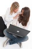 Jeunes femmes riantes avec l'ordinateur portable Photo stock