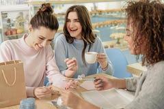 Jeunes femmes riantes hilares en café Image stock