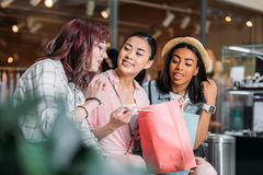 Jeunes femmes s'asseyant avec des paniers et parlant, concept de achat de jeunes filles Photo libre de droits