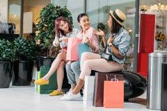 Jeunes femmes s'asseyant avec des paniers et parlant, concept de achat de jeunes filles Photos libres de droits