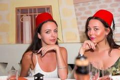 Jeunes femmes s'asseyant dans le restaurant marocain et les fezes de port Images stock