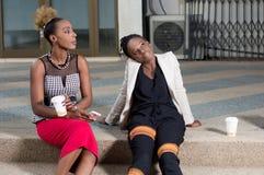 Jeunes femmes s'asseyant en dehors de leurs bureaux photographie stock libre de droits