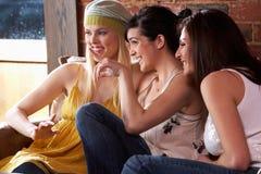 Jeunes femmes s'asseyant ensemble et parlant Photos stock
