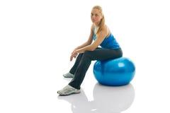 Jeunes femmes s'asseyant sur la bille de forme physique Photo stock