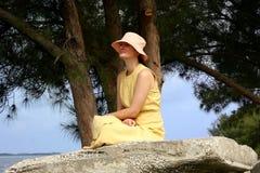 Jeunes femmes s'asseyant sur la roche sur le seacost Photo stock