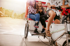 Jeunes femmes s'asseyant sur le tricycle et posant pour le selfie Images libres de droits