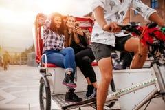 Jeunes femmes s'asseyant sur le tricycle et regardant le téléphone portable Photographie stock libre de droits