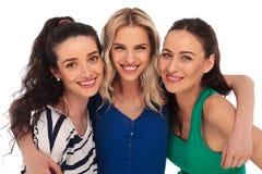3 jeunes femmes se jugeant étroit et le sourire Photographie stock