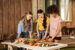 Jeunes femmes se tenant à la table et coupant les légumes frais sur le porche Image libre de droits