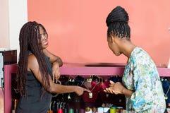 Jeunes femmes se tenant devant une fenêtre de magasin et montrant des bijoux photos stock
