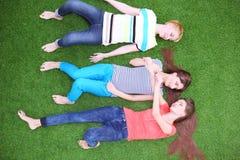 Jeunes femmes se trouvant sur l'herbe verte Jeunes femmes Photographie stock libre de droits