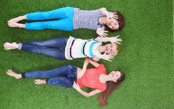 Jeunes femmes se trouvant sur l'herbe verte Jeunes femmes Photos stock