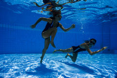 Jeunes femmes sportives courant sous l'eau Images libres de droits