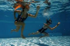 Jeunes femmes sportives courant sous l'eau Photographie stock libre de droits