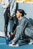 Jeunes femmes sportives dans les vêtements de sport se reposant avec des bouteilles de sports sur le stade Image stock