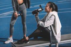 Jeunes femmes sportives en eau potable de vêtements de sport des bouteilles de sports sur le stade Images libres de droits