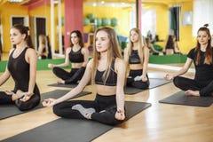 Jeunes femmes sportives pratiquant la leçon de yoga avec l'instructeur, s'asseyant dans l'exercice de Sukhasana Concept de bien-ê photo libre de droits