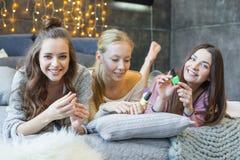 Jeunes femmes sur le lit Images stock