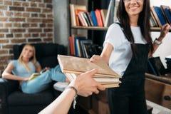 Jeunes femmes tenant la bibliothèque de livres à la maison Photos stock