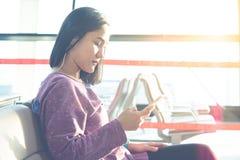Jeunes femmes textotant sur voler de attente de téléphone portable à la fenêtre d'aéroport Photos stock