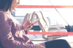 Jeunes femmes textotant sur voler de attente de téléphone portable à la fenêtre d'aéroport Images libres de droits