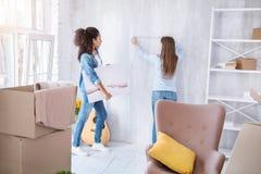Jeunes filles agréables mesurant le mur pour accrocher une photo image libre de droits