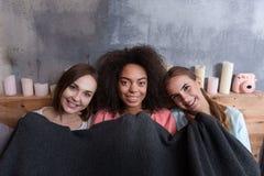 Jeunes filles agréables s'asseyant sur le lit à la maison Image stock