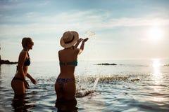 Jeunes filles attirantes se réjouissant, nageant en mer Images libres de droits