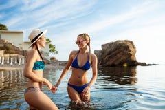 Jeunes filles attirantes se réjouissant, nageant en mer Images stock