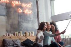 Jeunes filles avec plaisir prenant le selfie dans la chambre à coucher à la maison Photo stock