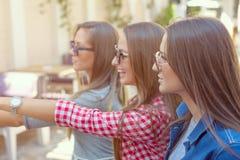 Jeunes filles ayant l'amusement au jour ensoleillé en café Photographie stock libre de droits