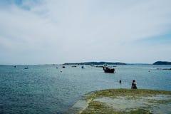 jeunes filles ayant un bain d'après-midi près de l'ancrage local avec le beau paysage marin photographie stock libre de droits