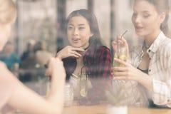 Jeunes filles buvant des cocktails ensemble tout en se reposant à la table en café Images libres de droits