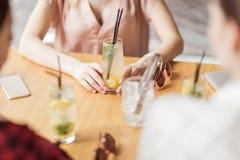 Jeunes filles buvant des cocktails ensemble tout en se reposant à la table en café Photographie stock libre de droits