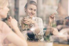 Jeunes filles buvant des cocktails ensemble tout en se reposant à la table en café Image stock