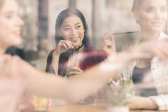 Jeunes filles buvant des cocktails ensemble tout en se reposant à la table en café Photo stock