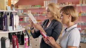 Jeunes filles choisissant le nouveau ton de vernis à ongles à la boutique cosmétique, meilleurs amis dans le supermarché Photo stock