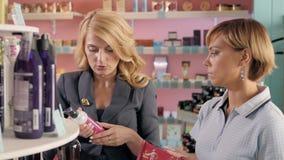 Jeunes filles choisissant le nouveau ton de vernis à ongles à la boutique cosmétique, meilleurs amis dans le supermarché Image libre de droits